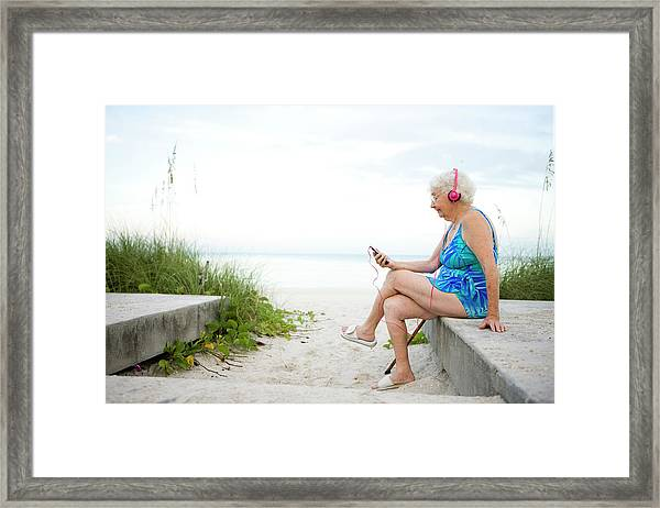 Senioir Woman Listening To An Mp3 Framed Print