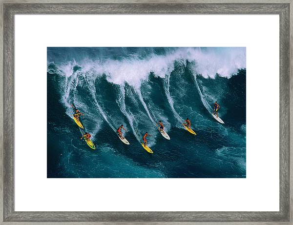 Seven Surfers Riding Large Wave Framed Print