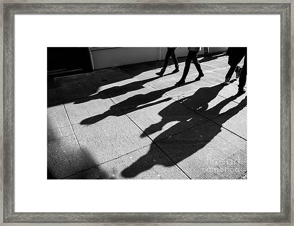 Shadows Of Four Walking Pedestrians Framed Print