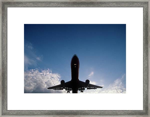 Silhouette Of A Jet Plane Landing Framed Print