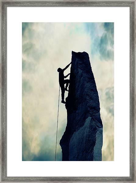 Silhouette Of Man Climbing Rock Framed Print