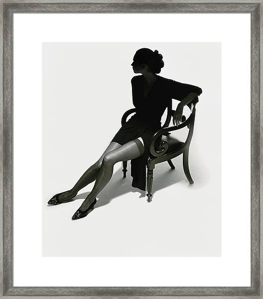 Silhouetted Woman On Chair Framed Print