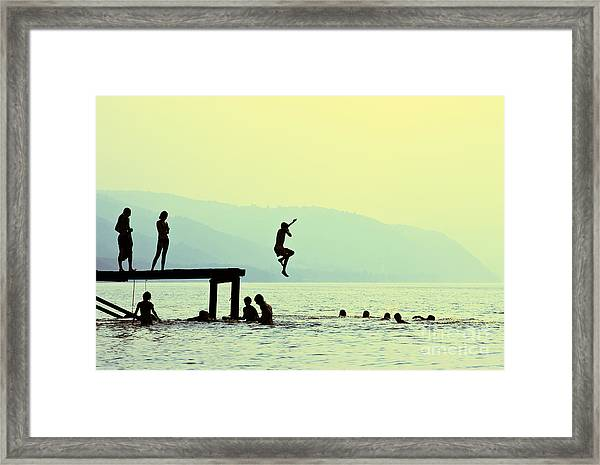 Silhouettes Of Kids Who Jump Off Dock Framed Print