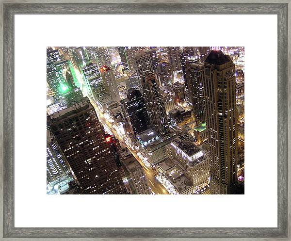 Skyscrapers Illuminated At Night Framed Print by By Ken Ilio