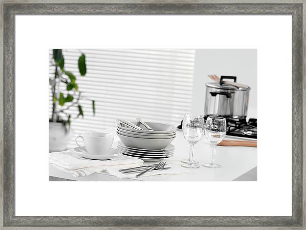 Stacked Dishes And Cutlery On Table Framed Print