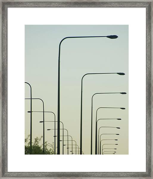 Streetlights Against Afternoon Sky Framed Print by By Ken Ilio