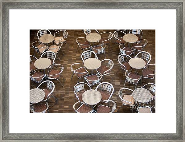 Tables And Chairs In A Restaurant Framed Print