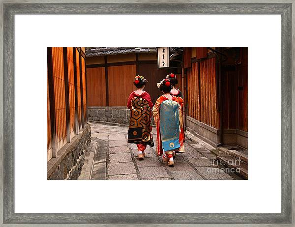 Three Geishas Walking On A Street Of Framed Print