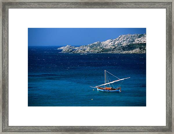 Traditional Sailboat On Rocky Coast Of Framed Print