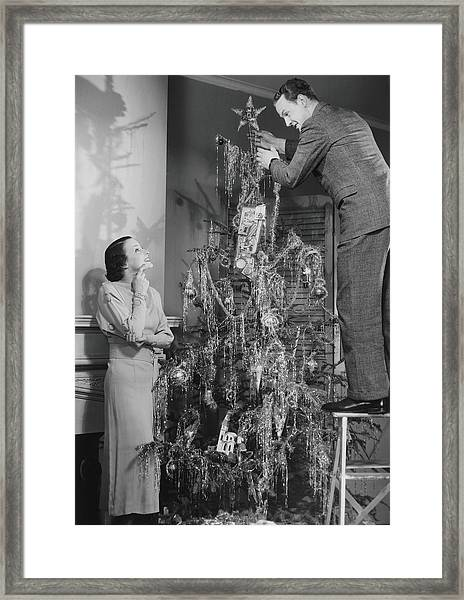 Woman Assisting Man Placing Star On Top Framed Print by George Marks