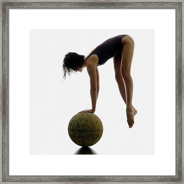 Woman Balancing On Globe Framed Print by Alfonse Pagano