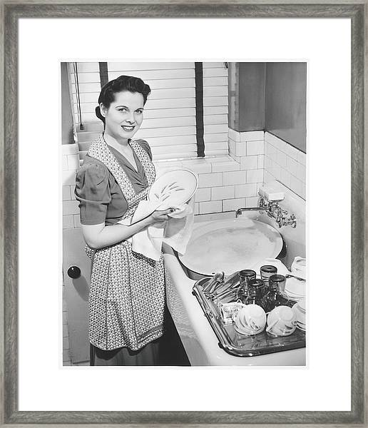 Woman Drying Dishes At Kitchen Sink Framed Print
