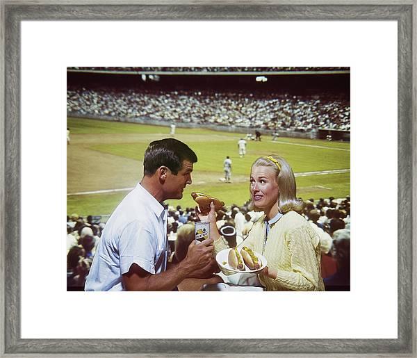 Woman Feeding Man Hot Dog, Smiling Framed Print