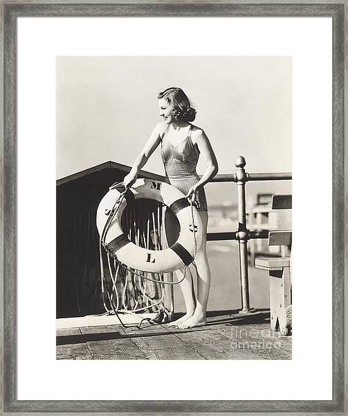 Woman On Pier Holding A Life Preserver Framed Print