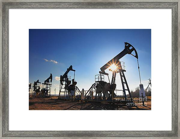Working Oil Pumps Silhouette Against Sun Framed Print