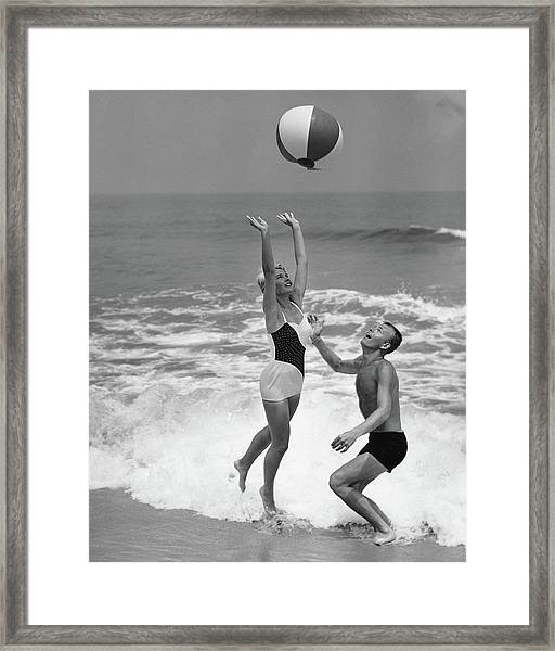 Young Couple Playing With Beach Ball At Framed Print by Stockbyte