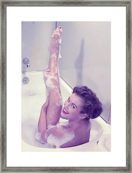 Young Woman In Bath Tub Lathering Framed Print by Hulton Archive