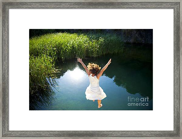 Young Woman In White Dress Jumping Into Framed Print