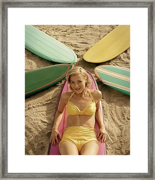 Young Woman Lying On Surfboard On Sand Framed Print