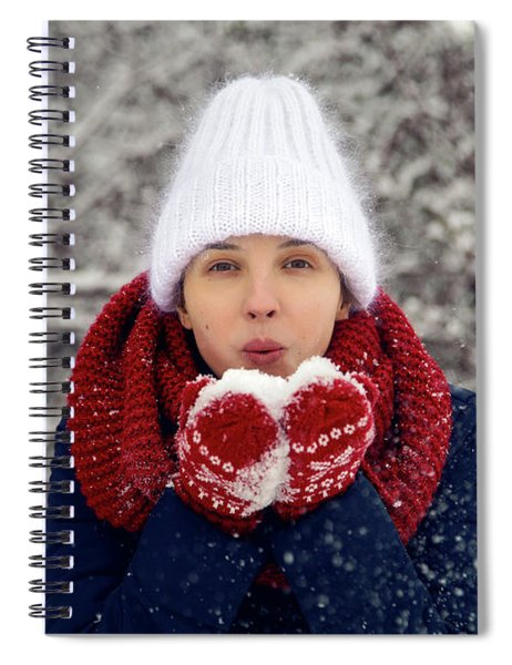 Young Girl In White Knitted Hat, Red Scarf And Mittens Blows Snow Spiral Notebook