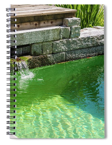 A Turquoise Green Garden Pond Is Framed By Rustic Stone Blocks, Green Plants, And A Deck. Spiral Notebook