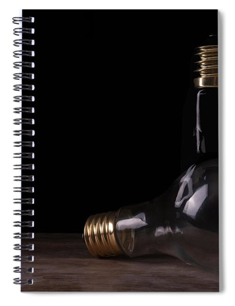 Two Light Bulbs Arranged On A Wooden Table  Spiral Notebook