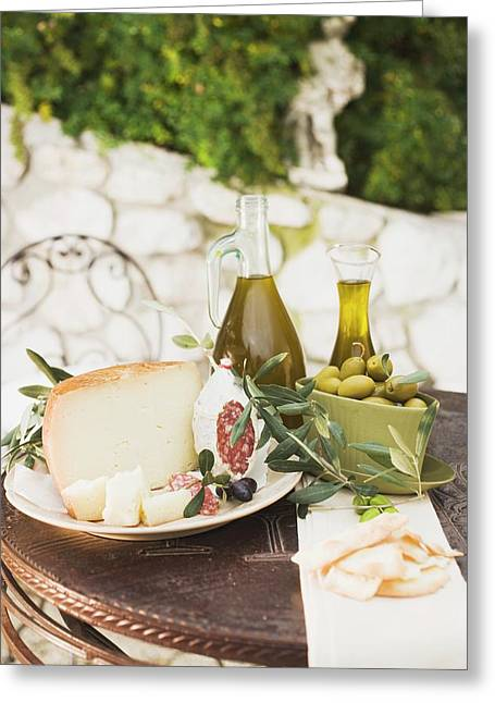 Cheese, Salami, Olives, Olive Oil, Crackers On Outdoor Table Greeting Card