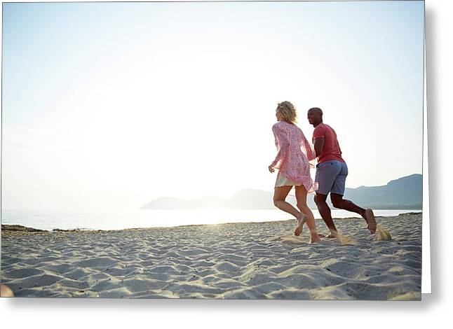 Couple Running On The Beach Greeting Card by Ruth Jenkinson