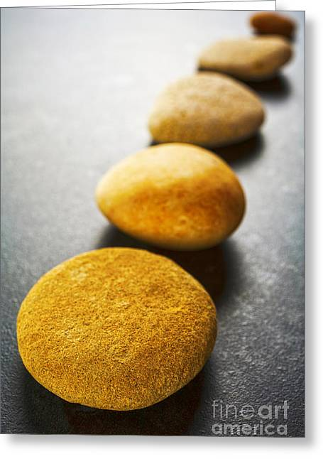Diagonal Line Of Brown Pebbles On Dark Background Greeting Card