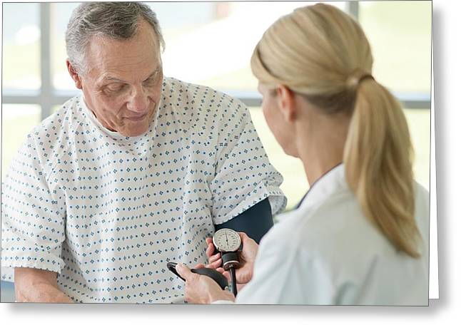 Female Doctor Taking Senior Man's Blood Pressure Greeting Card by Science Photo Library