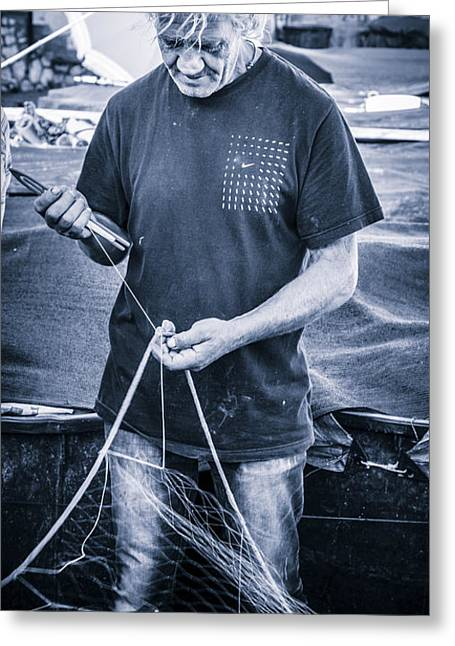 fisherman mending nets on Anzio harbour Greeting Card by Peter Noyce