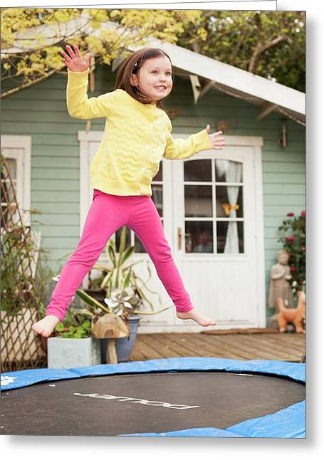 Girl Bouncing On A Trampoline Greeting Card by Ian Hooton