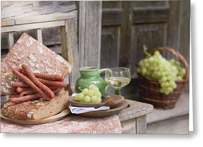 Grapes, Bread, Sausages And Wine On Wooden Bench In Front Of Farmhouse Greeting Card