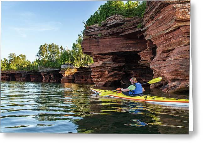 Kayaker Exploring The Sea Caves Greeting Card by Chuck Haney