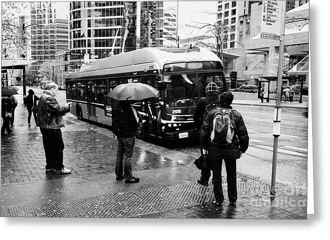 people standing in the rain waiting for a bus on burrard street downtown Vancouver BC Canada Greeting Card