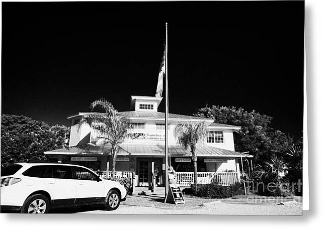 Raising The American Flag On A Flagpole Outside The Chamber Of Commerce Building In Key Largo Florid Greeting Card by Joe Fox