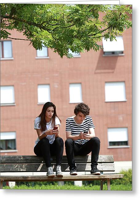 Teenage Couple Using Smart Phones Greeting Card
