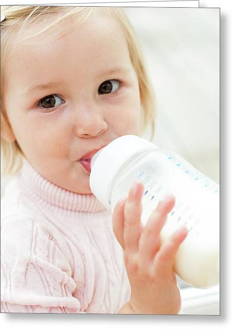 Toddler Holding A Bottle Of Milk Greeting Card by Ian Hooton