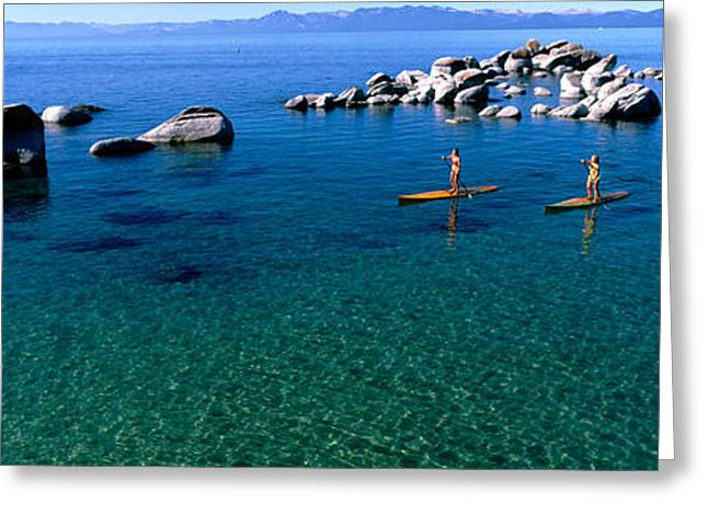 Two Women Paddle Boarding In A Lake Greeting Card by Panoramic Images