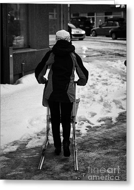 woman pushing kick sled out shopping on ice covered storgata main shopping street Honningsvag finnma Greeting Card