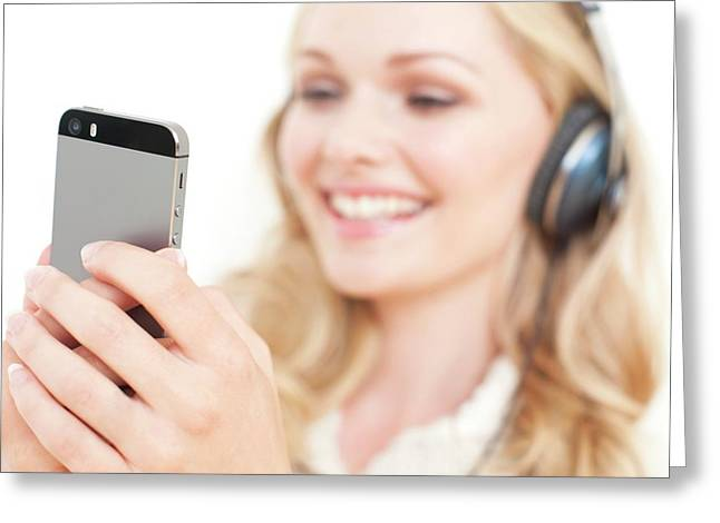 Woman Wearing Headphones Holding Smartpho Greeting Card by Ian Hooton