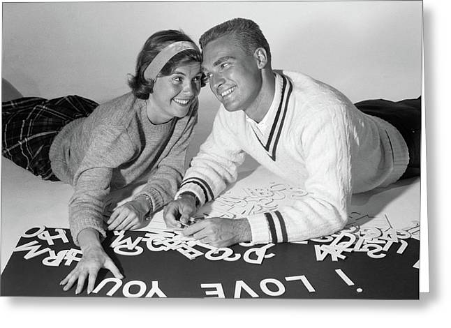 1960s Smiling Collegiate Couple Lying Greeting Card