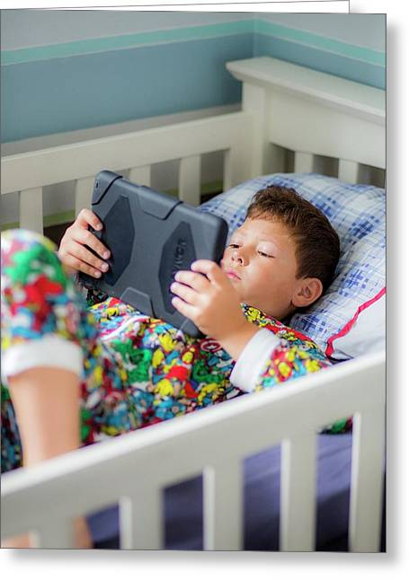 Boy In Bed Using A Digital Tablet Greeting Card