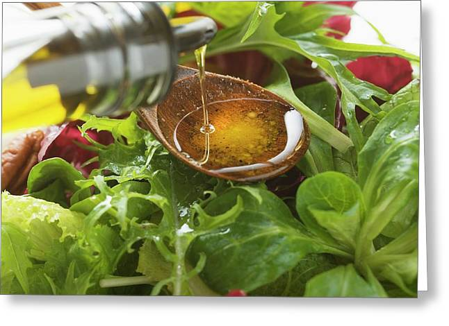 Pouring Olive Oil Into Wooden Spoon Above Salad Leaves Greeting Card