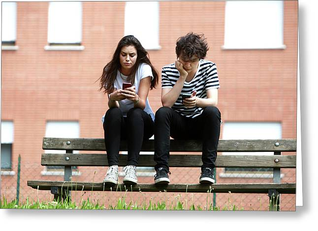 Teenage Couple Using Smart Phones Greeting Card by Mauro Fermariello