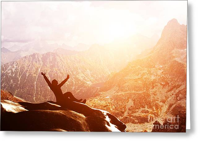 A Happy Man Sitting On The Peak Of A Mountain With Hands Raised At Sunset Greeting Card