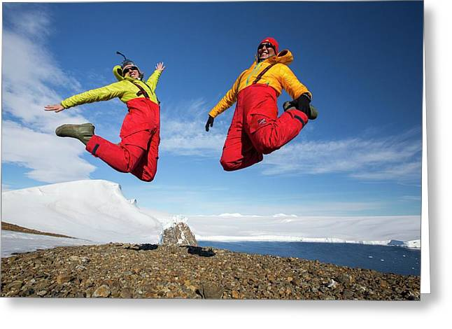 A Man And Woman Jumping For Joy Greeting Card by Ashley Cooper