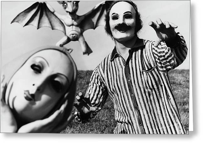 A Man And Woman Wearing Masks With A Bat Flying Greeting Card by Chadwick Hall