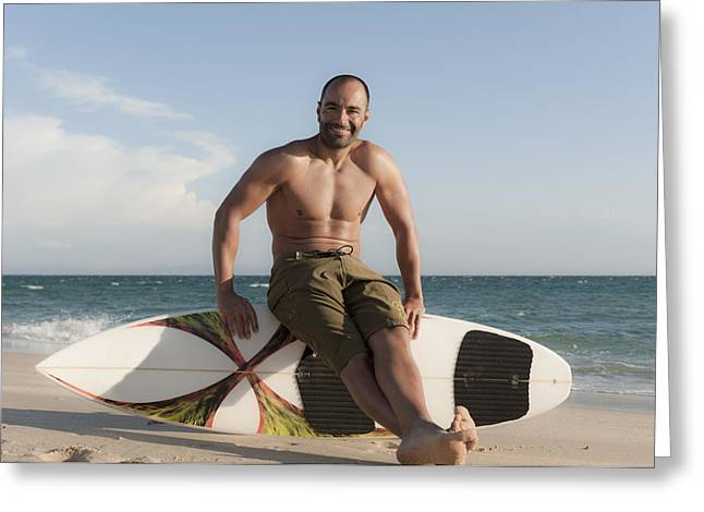 A Man Sits On His Surfboard On The Greeting Card by Ben Welsh
