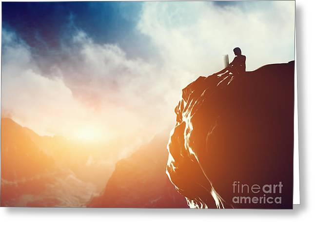 A Man Working On Laptop Sitting On The Peak Of A Mountain At Sunset Greeting Card